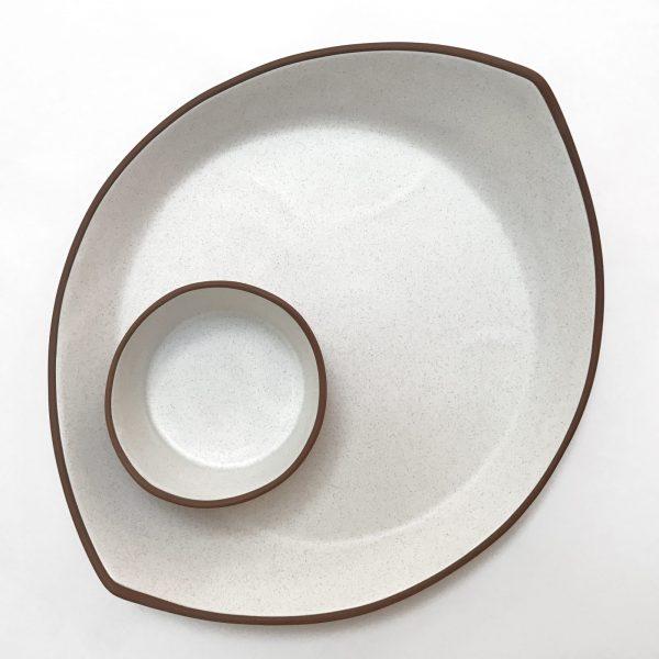 small white ceramic dish sitting on top of larger white ceramic platter